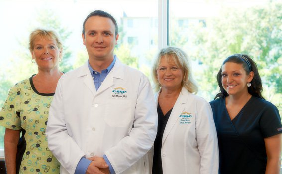 Esse Health medical team smiling in front of a window with greenery